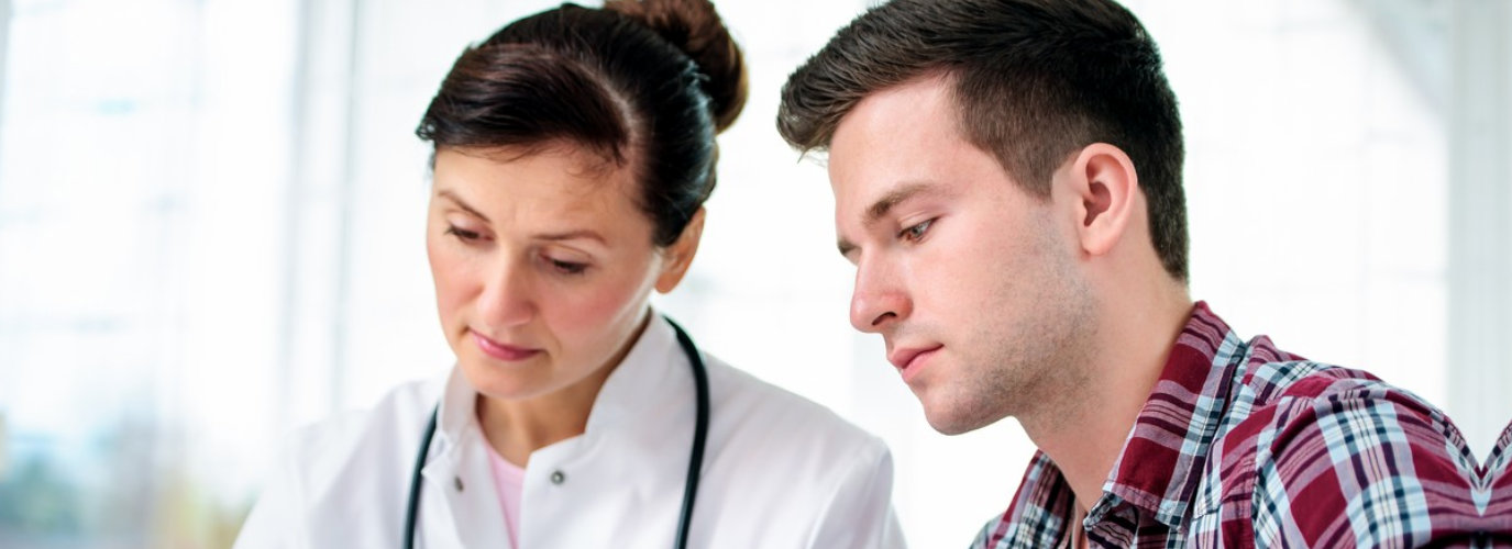 young man with her doctor looking at his medical test results